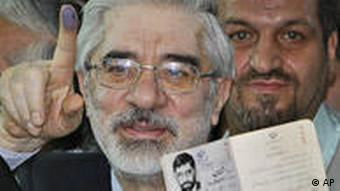 Mir Hossein Mousavi holds his inked finger and identity card aloft, as he prepared to cast his vote on June 12