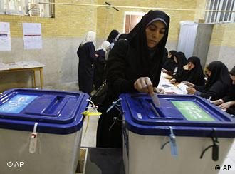 A woman in Tehran walks past election posters