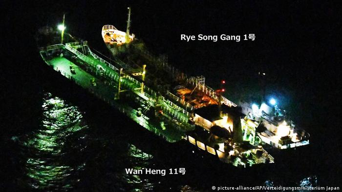 Two large tanker ships, side by side at sea, suspected of transferring banned goods.