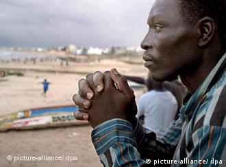 42 year old Mansour Seck from Senegal sits on Grand Yoff beach near fishing vessels similar to the types used by immigrants in Dakar, Senegal Friday 15 September 2006. Mansour Seck like some 20,000 other West African illegal migrants this year, has tried to go beyond the Spanish Canary Islands, in the hopes of reaching mainland Spain. Frustrated by the limited opportunities at home, Seck sold his house and left his wife and children in May on a fishing vessel in the hopes of reaching mainland Spain. On his second attempt, the unemployed fisherman, father of two, embarked on the journey with his eight brothers and 83 other passengers in a fishing vessel, before having to return due to problems with the boat. In his modest room in Grand Yoff, a district of the Dakar capital, Seck dreams of leaving again. EPA/PIERRE HOLTZ +++(c) dpa - Bildfunk+++ ,