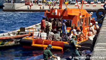 A fishing boat tied to a rescue ship with 44 African immigrants on board is seen arriving at the port of San Sebastian de La Gomera, on the Spanish Canary Island of La Gomera