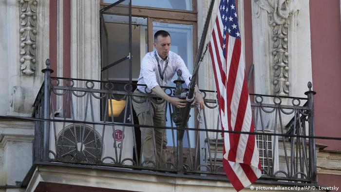 A consulate staff member unties the flag lanyards on the Sankt Petersburg consulate balcony (picture alliance/dpa/AP/D. Lovetsky)