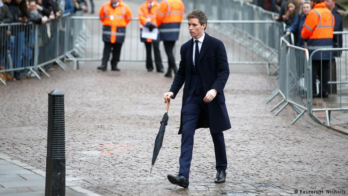 Eddie Redmayne, using an umbrella as a walking stick, arrives at the Great St. Marys Church in Cambridge for Stephen Hawking's funeral.