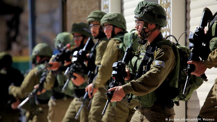 Israeli forces stand with guns as Palestinians protest on the Gaza-Israel border