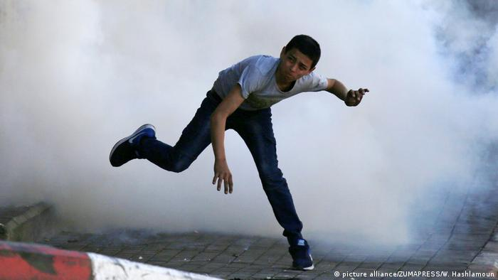 A Palestinian protester throws back a tear gas canister fired by Israeli security forces in clashes in March