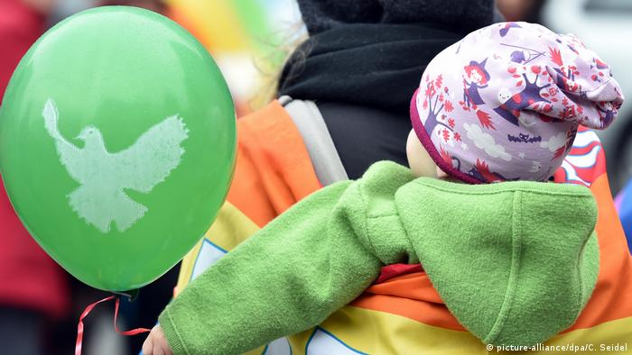 A small child holds a balloon with a dove on it (picture-alliance/dpa/C. Seidel)