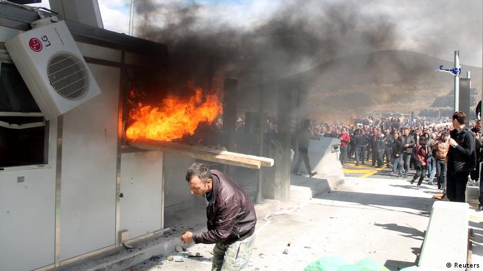 A toll booth burns as a crowd looks on.