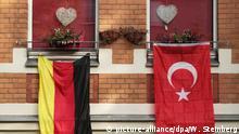 Eine rote, türkische Fahne mit dem Halbmond und dem Stern hängt während der Fußball-EM 2016 am 14.06.2016 in Berlin an einem Haus neben der deutschen Flagge in Schwarz-Rot-Gold. Foto: Wolfram Steinberg/dpa | Verwendung weltweit