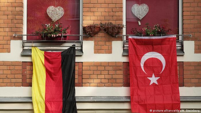 Symbolbild deutsche und türkische Fahnen nebeneinander
