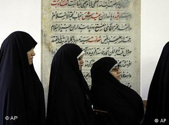 Women wearing chadors wait in line to vote