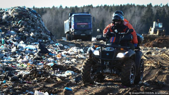 Man wearing a gas mask rides a quad bike at the landfill