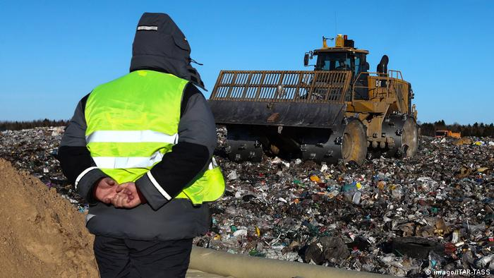 Man watching a roller driving over garbage in Yadrovo
