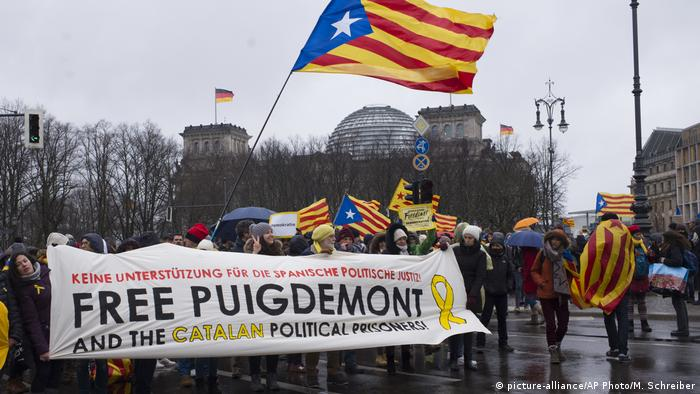 Demonstrators in front of the Reichstag building wave the estelada and hold a sign demanding the release of Carles Puigdemont