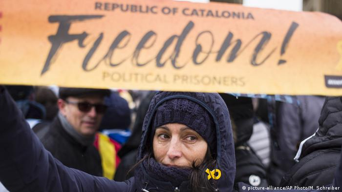 A demonstrator holds up a sign demanding freedom for Catalan politicians in jail (picture-alliance/AP Photo/M. Schreiber)