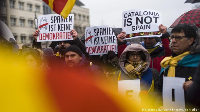 Protesters hold signs saying 'Spain is not a democracy' and declaring support for Catalan independence