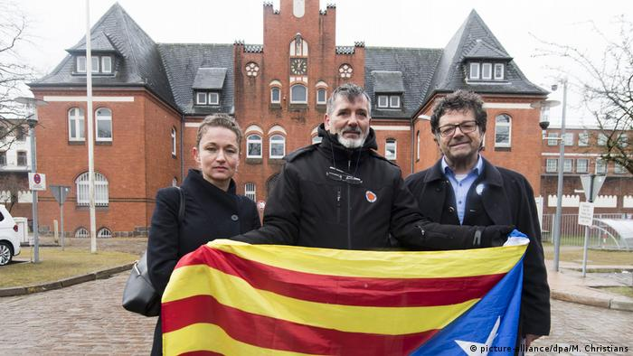 Nastic, a demonstrator from Spain and Dehm (L to R) stand with the 'estelada,' the flag of Catalan independence, in front of the prison where Puigdemont is being held