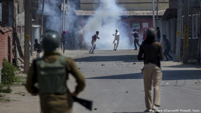 Kashmiri protesters engulfed in tear gas smoke clash with Indian paramilitary soldiers during a protest against the killing of rebels in Srinagar, Indian controlled Kashmir, Sunday, April 1, 2018