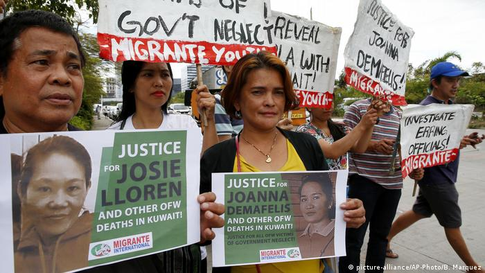 Protesters in the Philippines hold photos of loved ones who were killed working as domestic workers overseas.
