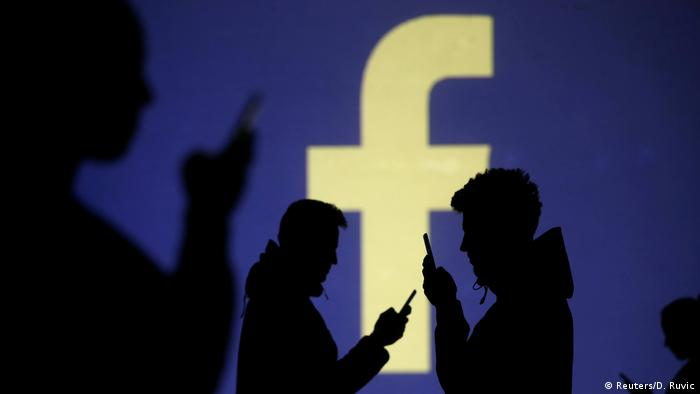 Silhouettes of cellphone users in front of a screen displaying the Facebook logo (Reuters/D. Ruvic)