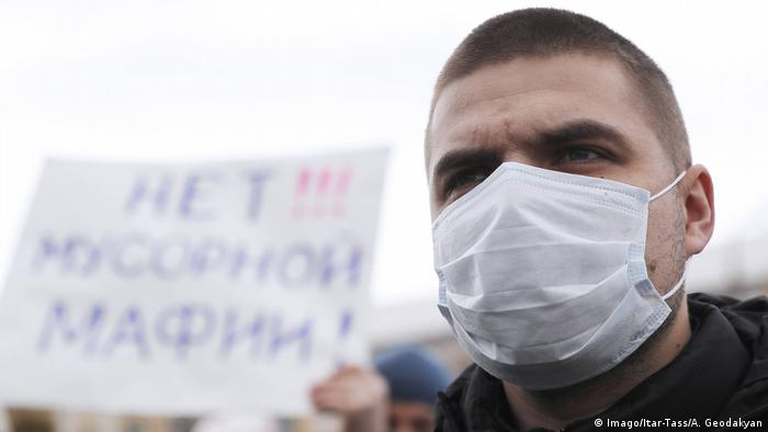 Protester wearing a breathing mask with a placard barely visible in the background