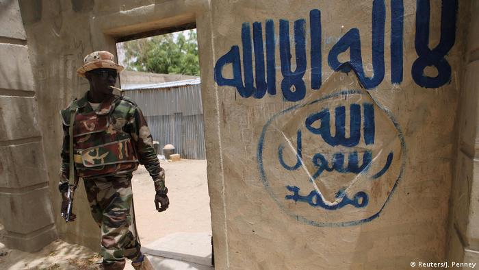A Nigerian soldier walks out of a house that residents say a Boko Haram militant had forcefully seized and occupied in Damasak