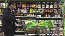 April 2, 2018*** A man pushes a shopping cart past a display of nuts imported from the United States and other countries at a supermarket in Beijing, Monday, April 2, 2018. China raised import duties on a $3 billion list of U.S. pork, fruit and other products Monday in an escalating tariff dispute with President Donald Trump that companies worry might depress global commerce. (AP Photo/Andy Wong)  