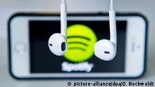 ARCHIV - ILLUSTRATION- 17.03.2014, Berlin: Kopfhörer hängen vor einem Apple Iphone 5s, auf dem das Logo vom Musik-Streaming-Dienst Spotify angezeigt wird. Spotify will zum Jahresende auf rund 200 Millionen Nutzer wachsen. (zu dpa Spotify will Ende des Jahres rund 200 Millionen Nutzer haben vom 26.03.2018) Foto: Daniel Bockwoldt/dpa +++(c) dpa - Bildfunk+++ | Verwendung weltweit
