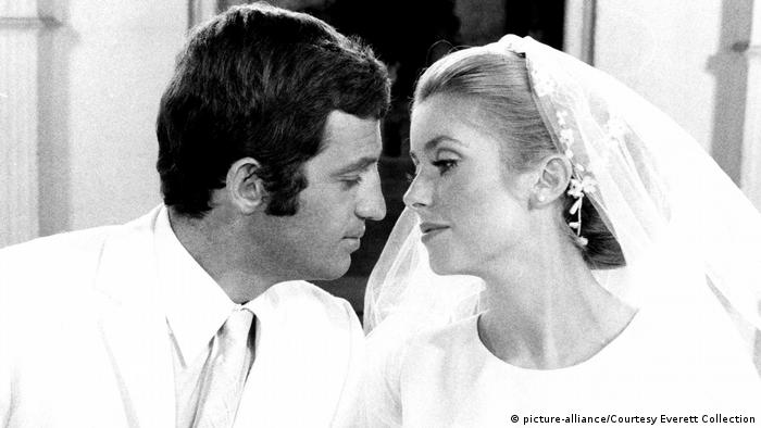 Jean-Paul Belmondo and Catherine Deneuve lean in to kiss one another