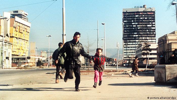 Otac i dijete trče kroz Sarajevo u opsadi