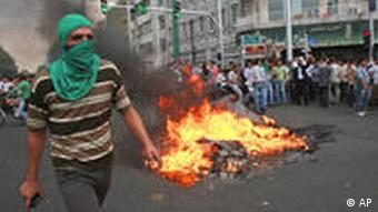 A masked supporter of Iranian reformist presidential candidate Mir Hossein Mousavi walks past burning rubbish
