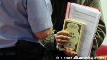 Murat K. (M) kommt am 20.01.2014 in Bonn (Nordrhein-Westfalen) in den Gerichtssaal im Landgericht und hält einen Koran sowie ein Merkblatt zum Grundgesetz der Bundesrepublik Deutschland. Wegen seiner Messerattacken auf Polizisten steht der Islamist erneut vor Gericht. Der Mann war bereits im Oktober 2012 zu einer sechsjährigen Haftstrafe verurteilt worden. Der Bundesgerichtshof (BGH) hatte den Schuldspruch bestätigt, aber das Strafmaß wegen Rechtsfehlern aufgehoben. Foto: Oliver Berg/dpa (zu dpa Strafe für Islamisten wegen Angriff auf Polizisten wird verhandelt vom 20.01.2014) +++(c) dpa - Bildfunk+++ |