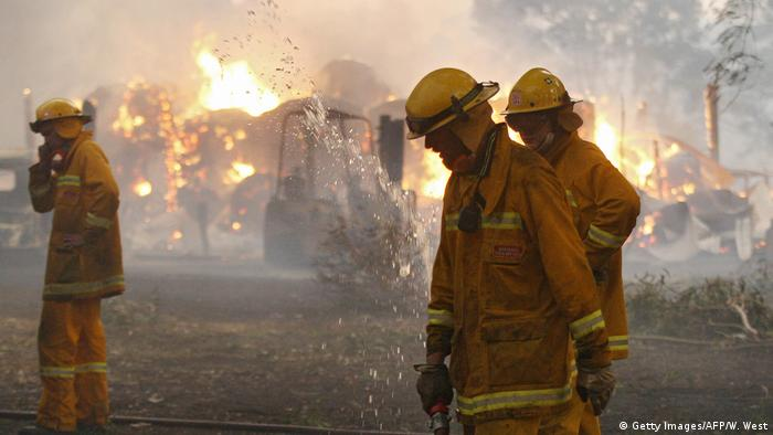 Volunteer firefighters pack away their hoses as a barn burns in the background in the 2009 Australian bushfires