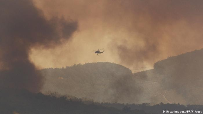 A fire-fighting helicopter, shrouded in smoke, flies above the mountains