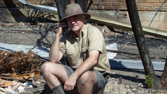 David Barton sits outside the burnt-out remains of his home