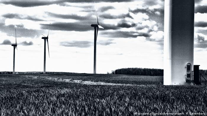 Black/white photo: Wind turbines standing on a field (picture-alliance/chromorange/K. H. Spremberg)