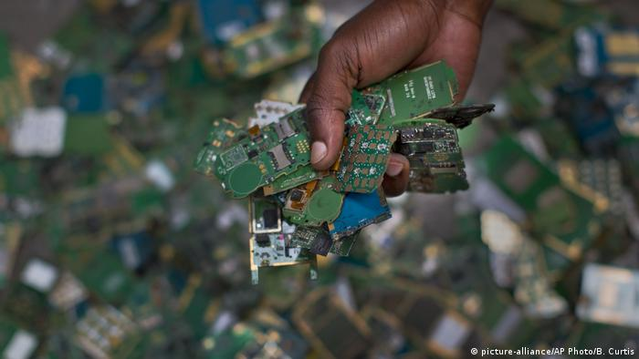 A hand holds several cellphone printed circuit boards (photo: picture-alliance/AP Photo/B. Curtis)