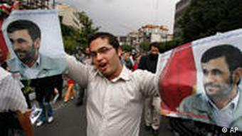 A supporter of the President Mahmoud Ahmadinejad holds posters of him