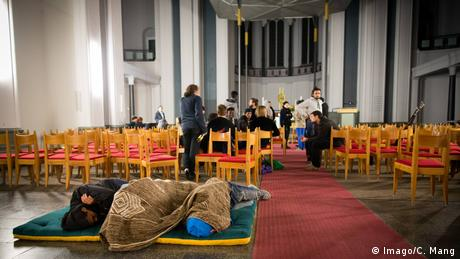 Several persons in blankets, lying on a mattress among church benches (Imago/C. Mang)