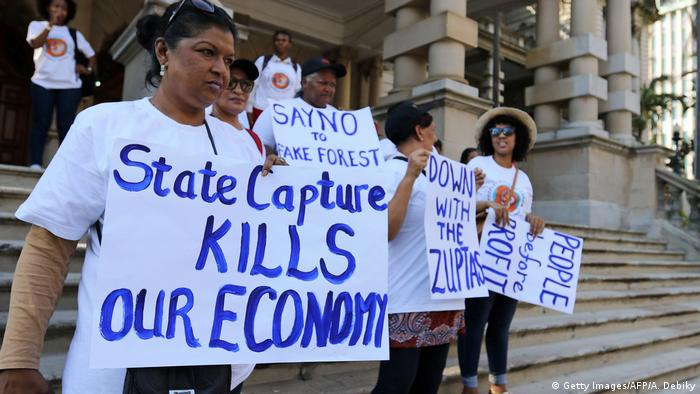 A group of women holding up placards that read 'State capture kills our economy' (Getty Images/AFP/A. Debiky)