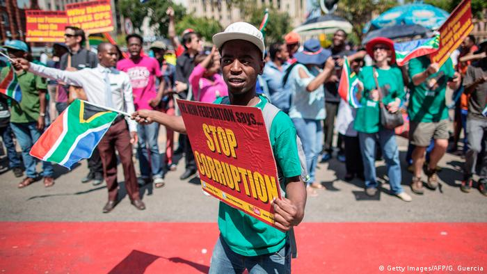 A young South African protester waves a South African flag and holds a sign which reads 'stop corruption'