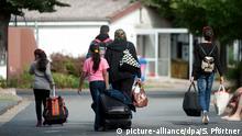 ARCHIV - Flüchtlinge mit Koffern und Plastiktüten gehen am 27.08.2013 im Grenzdurchgangslager Friedland (Niedersachsen) an Unterkünften vorbei. (zu dpa (zu dpa «UNHCR wirbt im Bundestag für Familiennachzug zu allen Flüchtlingen» vom 29.01.2018) Foto: Swen Pförtner/dpa +++(c) dpa - Bildfunk+++ | Verwendung weltweit