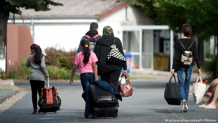 A refugee family pulling suitcases