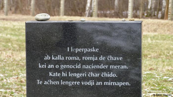Auf einem schwarzen Gedenkstein prangen fünf Zeilen einer weißen Schrift in der Sprache Romanes. Auf dem Stein liegen einige Steine, im Hintergrund ist eine Wiese und der untere Rand eines Birkenwäldchens zu erahnen