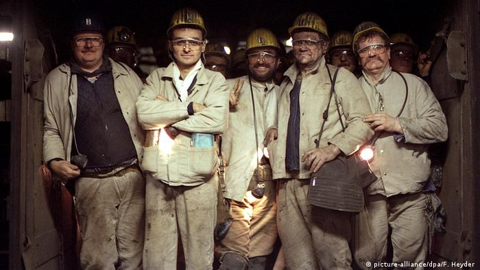 Five coal miners in full gear