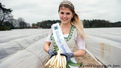 Spargelkönigin im spargelfeld, hält Spargelstangen in der Hand (picture-alliance/dpa/S. Stein)