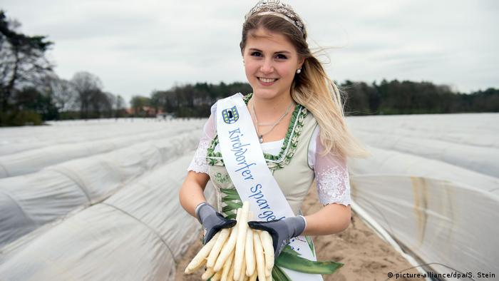 Young woman with a crown holding asparagus in a field (picture-alliance/dpa/S. Stein)