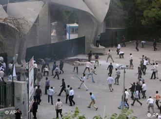 Iranian supporters of President Mahmoud Ahmadinejad hurl stones towards opposition supporters