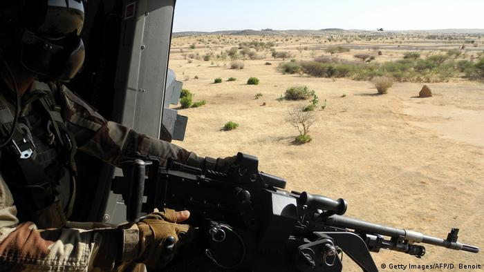 A masked soldier with an assault rifle looks out over a field where trees are scattered.