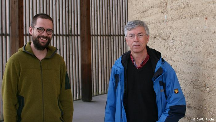 Two men stand in front of a wall