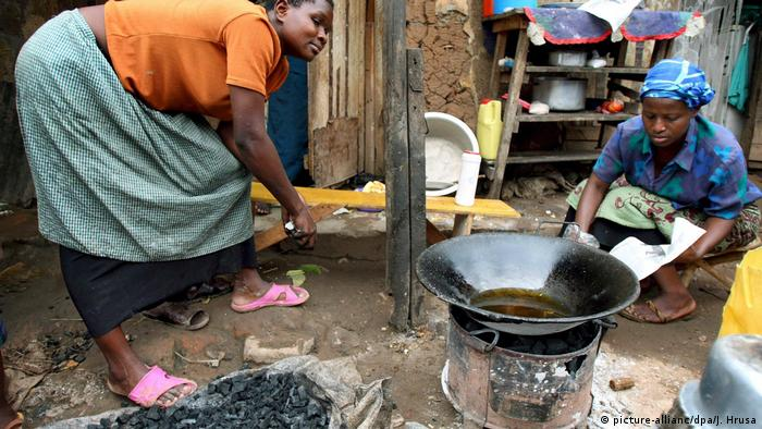 Two women cook over a charcoal fire in Kampala, Uganda
